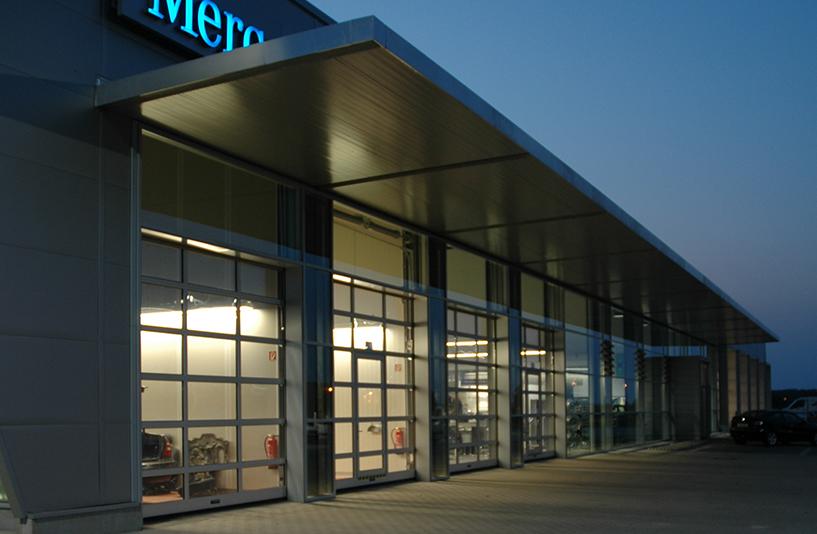 Mercedes-Benz Herbrand – Außenansicht der Werkstatttore bei Dämmerung